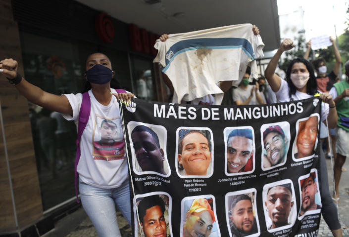 """Mothers, who said their sons were killed during police operations, holds a banner with the photos of their sons, during a protest against crimes committed by the police against black people in the favelas, Rio de Janeiro, Brazil, Sunday, May 31, 2020. The protest, called """"Black lives matter,"""" was interrupted when police used tear gas to disperse people. """"I can't breathe"""", said some of the demonstrators, alluding to the George Floyd's death. (AP Photo/Silvia Izquierdo)"""