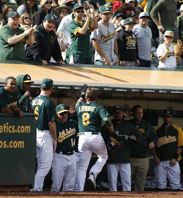 Oakland Athletics' Jed Lowrie (8) is greeted in the dugout after scoring against the Minnesota Twins during the first inning of a baseball game, Saturday, Sept. 21, 2013, in Oakland, Calif. (AP Photo/George Nikitin)