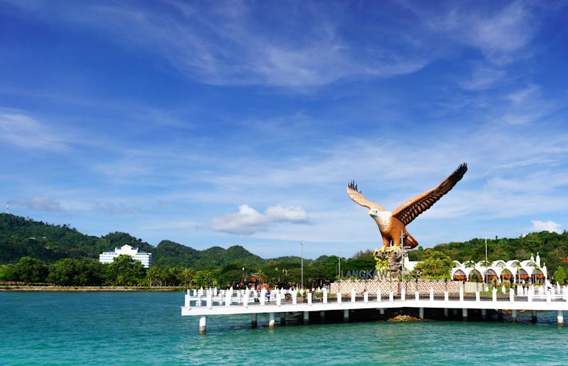 Shot of Langkawi's famous landmark the Eagle square, Dataran Lang, from the sea in front of it. The blue cloudy sky and beautiful blue water show how Malaysia's beauty