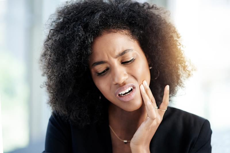 Shot of a young businesswoman suffering from toothache at work
