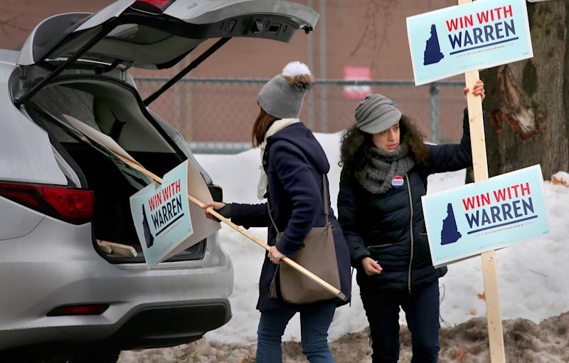 MANCHESTER, NH - FEBRUARY 11: Elizabeth Warren volunteers Meredith Osborn and Krystal Lay deliver signs to other volunteers outside a polling place on election day in Manchester, NH on Feb. 11, 2020. The first-in-the-nation New Hampshire primary is today. (Photo by Lane Turner/The Boston Globe via Getty Images)
