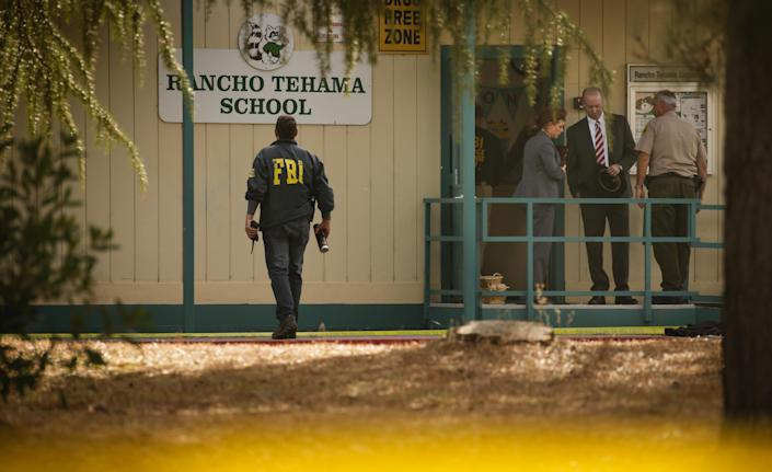 FBI agents are seen behind yellow crime scene tape outside Rancho Tehama Elementary School after a shooting in the morning on Nov. 14, 2017, in Rancho Tehama, Calif. (Photo: Elijah Nouvelage/AFP/Getty Images)