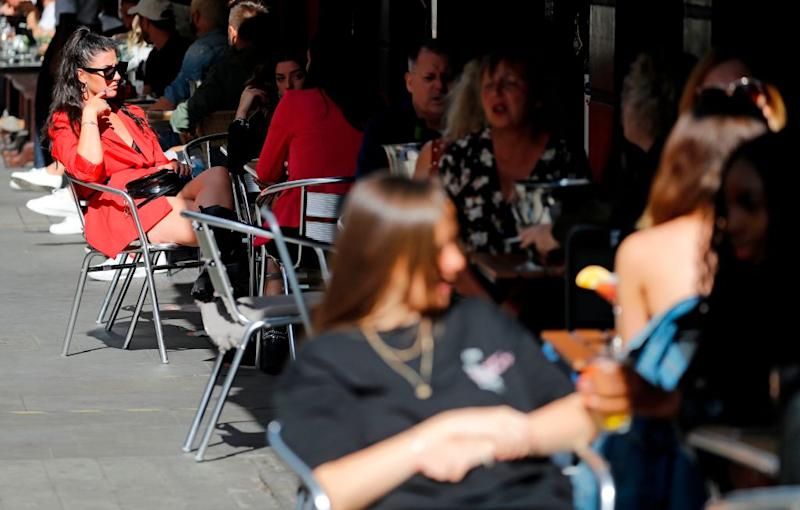Diners enjoy their drinks as they sit at tables outside a restaurant in London following the government's offer. Source: Getty