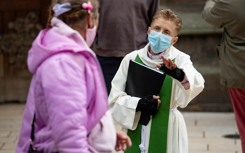 A priest wearing PPE speaks to a member of the St Martin congregation in Birmingham city centre - PA