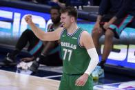 Dallas Mavericks' Luka Doncic (77) celebrates a basket scored by Dorian Finney-Smith in the second half of an NBA basketball game against the Memphis Grizzlies in Dallas, Monday, Feb. 22, 2021. (AP Photo/Tony Gutierrez)