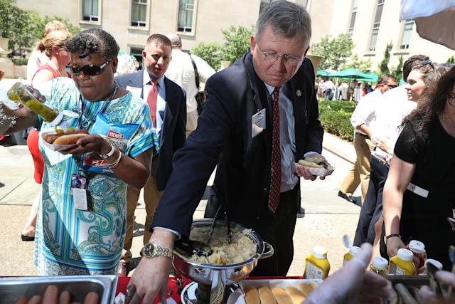 Rep. Frank Lucas (R-Okla.) prepares a hot dog during the American Meat Institute's annual Hot Dog Lunch in the Rayburn Office Building courtyard on July 19, 2017.