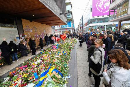 People lay flowers near the crime scene at Ahlens department store at the pedestrian street Drottninggatan in central Stockholm