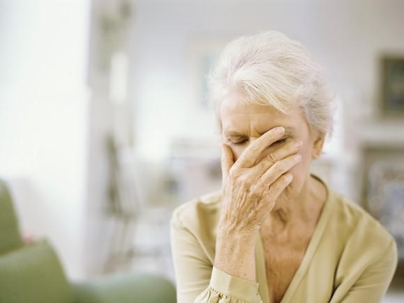 Senior woman with hand over her face