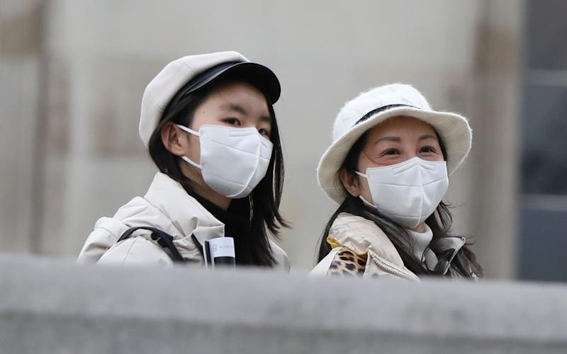 Two women walk through London's Trafalgar Square wearing protective facemasks on the day that Heath Secretary Matt Hancock said that the number of people diagnosed with coronavirus in the UK has risen to 51. (Photo by Luciana Guerra/PA Images via Getty Images)