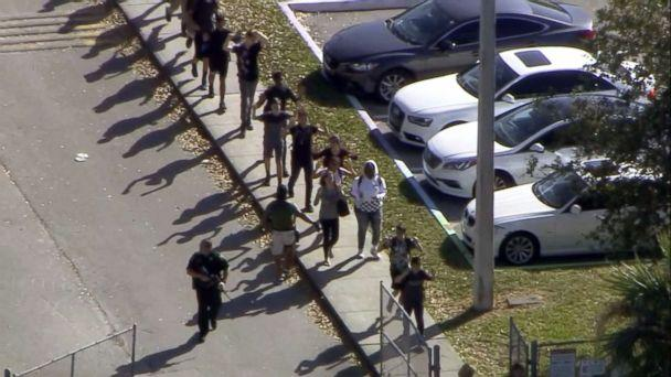 PHOTO: Students walk with an armed escort after after reports of a shooting at Stoneman Douglas High School in Parkland, Fla., Feb. 14, 2018. (WPLG)
