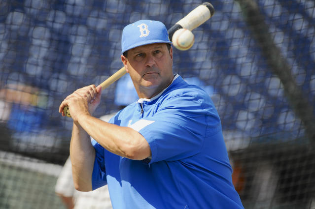 FILE - In this June 14, 2013, file photo, UCLA coach John Savage eyes the ball during NCAA college baseball practice at TD Ameritrade Park in Omaha, Neb. A new rule intended to help speed up the game also could thwart attempts to steal signs in college baseball. The NCAA will allow a pitcher to wear a wristband with a signal card when the season opens Friday, Feb. 14, 2020, allowing him and the catcher to look into the dugout to get pitch calls and eliminating the need for the catcher to relay the call with hand signs. (AP Photo/Eric Francis, File)