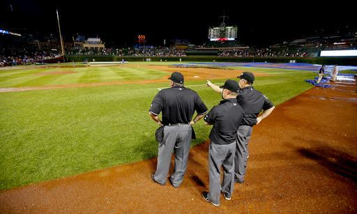 The umpires look over the field after a heavy rain soaked Wrigley Field during a baseball game between the San Francisco Giants and the Chicago Cubs in the fifth inning Tuesday, Aug. 19, 2014, in Chicago. (AP Photo/Jeff Haynes)