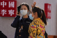 """Shoppers wearing masks to protect from the coronavirus walk by the words """"China Li-Ning"""" for Chinese sports goods brand Li-Ning in Beijing on Sunday, Oct. 4, 2020. This year, travel restrictions due to the coronavirus pandemic mean that some 600 million tourists — about 40% of the population — will travel within China during the weeklong National Day holidays that began last Thursday, according to Ctrip, China's largest online travel agency. (AP Photo/Ng Han Guan)"""