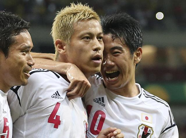 FILE - In this June 19, 2013 file photo, Japan's Keisuke Honda is congratulated by his teammates Shinji Kagawa, right, and Yuto Nagatomo, left, after scoring the opening goal during the soccer Confederations Cup group A match between Italy and Japan in Recife, Brazil. Honda and Kagawa are Japan's biggest stars and the heart of their team's attack. (AP Photo/Antonio Calanni, File)
