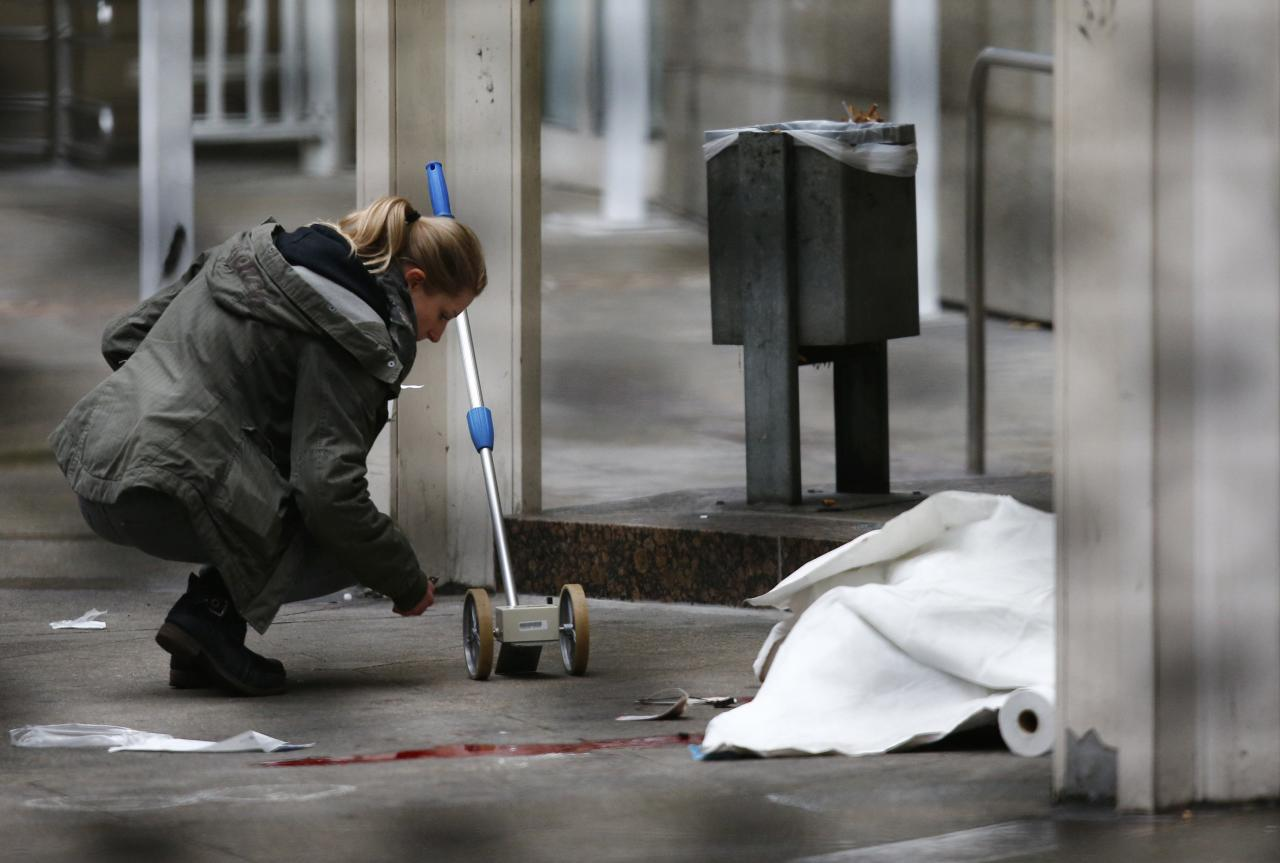 A police officer examines the crime scene next to a covered body following a shooting at the entrance of Building E of the courthouse in Frankfurt January 24, 2014. REUTERS/Ralph Orlowski (GERMANY - Tags: CRIME LAW TPX IMAGES OF THE DAY)