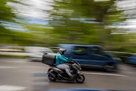 A delivery worker rides his motorbike in Madrid, Spain, Tuesday, May 11, 2021. Spain has approved a pioneering law that gives delivery platforms a mid-August deadline to hire the workers currently freelancing for them and that requires transparency of artificial intelligence to manage workforces. (AP Photo/Manu Fernandez)