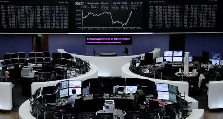 Traders work in front of the German share price index DAX board at the stock exchange in Frankfurt