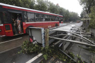 <strong>A bus drives past a damaged bus stand in Mumbai.</strong> (AP Photo/Rafiq Maqbool)