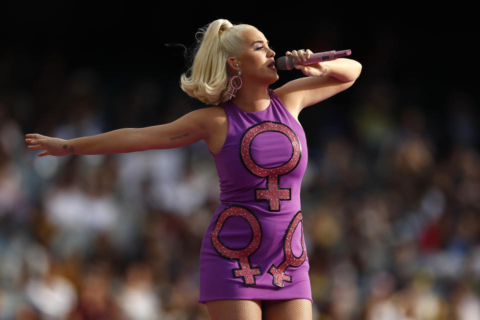Perry's third and final look during her ICC Women's T20 Cricket World Cup Final performance was this purple mini dress with the women's gender symbol emblazoned across the front and matching earrings. (Getty Images)