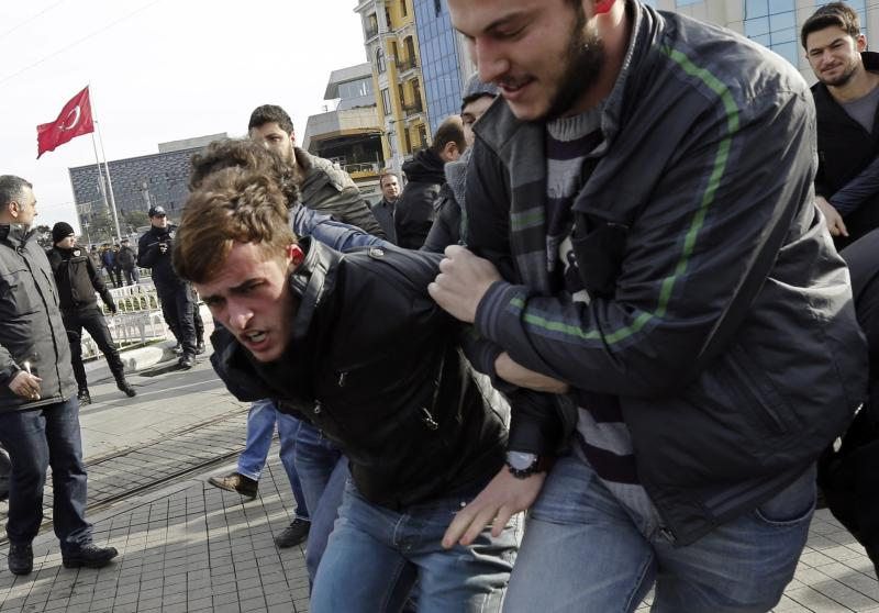 Plain clothes police officers detain an anti-government protester at Taksim square in central Istanbul