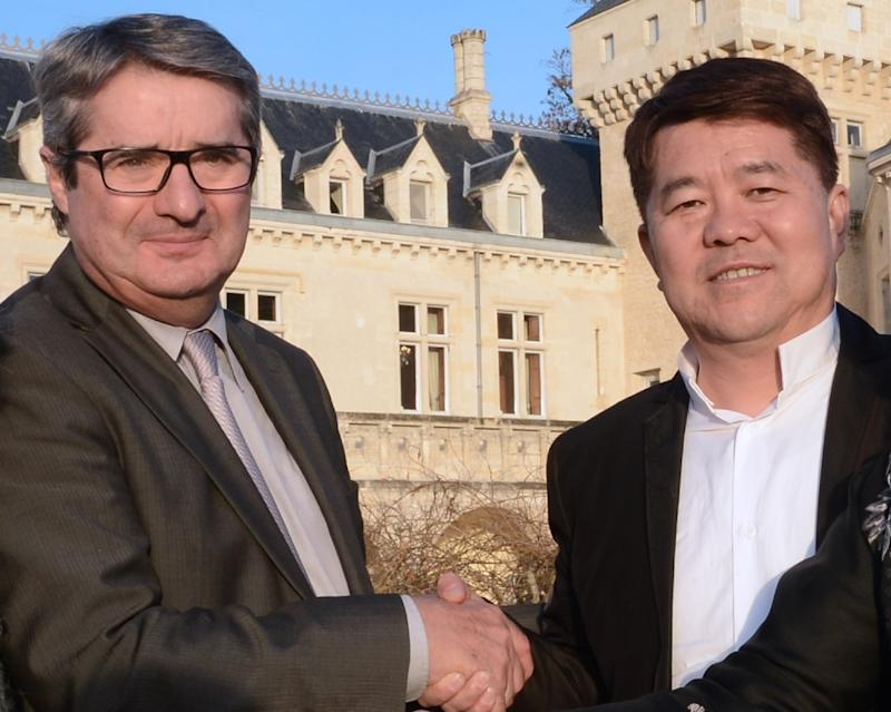 Late Chinese billionaire Lam Kok (R) shaking hands with the late French former owner of the Chateau de La Riviere James Gregoire in front of the castle in La Riviere, hours before they were killed in a helicopter crash