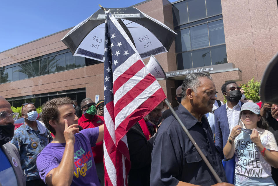 The Rev. Jesse Jackson leads protesters outside the office of U.S. Sen. Kyrsten Sinema, D-Arizona, on Monday, July 26, 2021, in Phoenix. Jackson was among 35 people arrested for refusing to leave Sinema's office while protesting her opposition to ending the filibuster to pass voting rights legislation. (AP Photo/Jonathan J. Cooper)