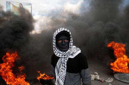 A Palestinian demonstrator stands near burning tires during clashes with Israeli troops at a protest against U.S. President Donald Trump's decision to recognise Jerusalem as the capital of Israel, near the West Bank city of Nablus December 15, 2017. REUTERS/Mohamad Torokman