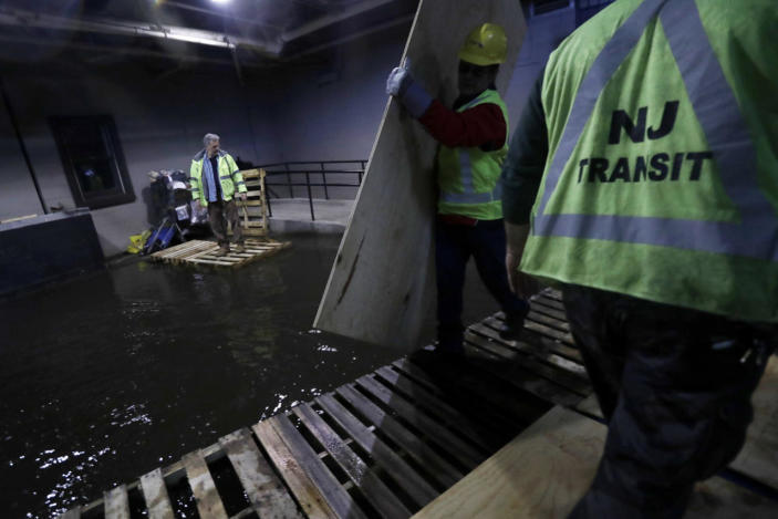 <p>New Jersey Transit workers lay down pallets and boards for commuters to walk on a flooded hallway adjacent to the site of a train crash at the Hoboken Terminal, Sept. 30, 2016, in Hoboken, N.J. Commuters are using alternative travel in and out of Hoboken a day after a commuter train crashed into the rail station, killing one person and injuring more than 100 people. (Photo: Julio Cortez/AP)</p>