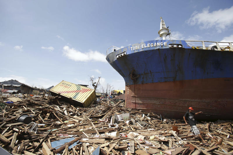 FILE - In this Nov. 10, 2013 file photo, a survivor walks by a large ship after it was washed ashore by strong waves caused by powerful Typhoon Haiyan in Tacloban city, Leyte province, central Philippines. Freaky storms like 2013's Typhoon Haiyan, 2012's Superstorm Sandy and 2008's ultra-deadly Cyclone Nargis may not have been caused by warming, but their fatal storm surges were augmented by climate change's ever rising seas, Maarten van Aalst, a top official at the International Federation of Red Cross and Red Crescent Societies said. Global warming is driving humanity toward a whole new level of many risks, a United Nations scientific panel reports, warning that the wild climate ride has only just begun. (AP Photo/Aaron Favila, File)