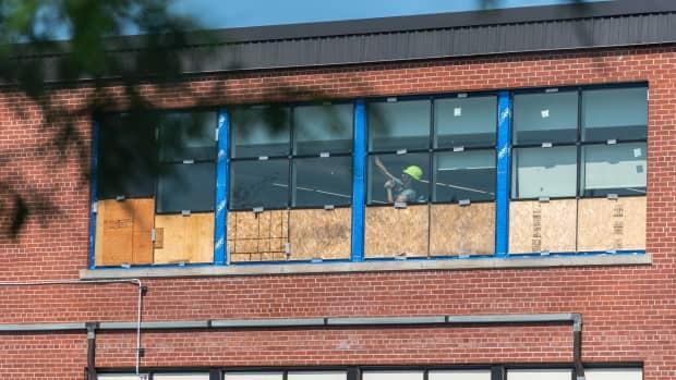 A worker tends to the windows at Ottawa's Woodroffe Avenue Public School on Thursday, about two weeks before the start of class. (Alexander Behne/CBC - image credit)