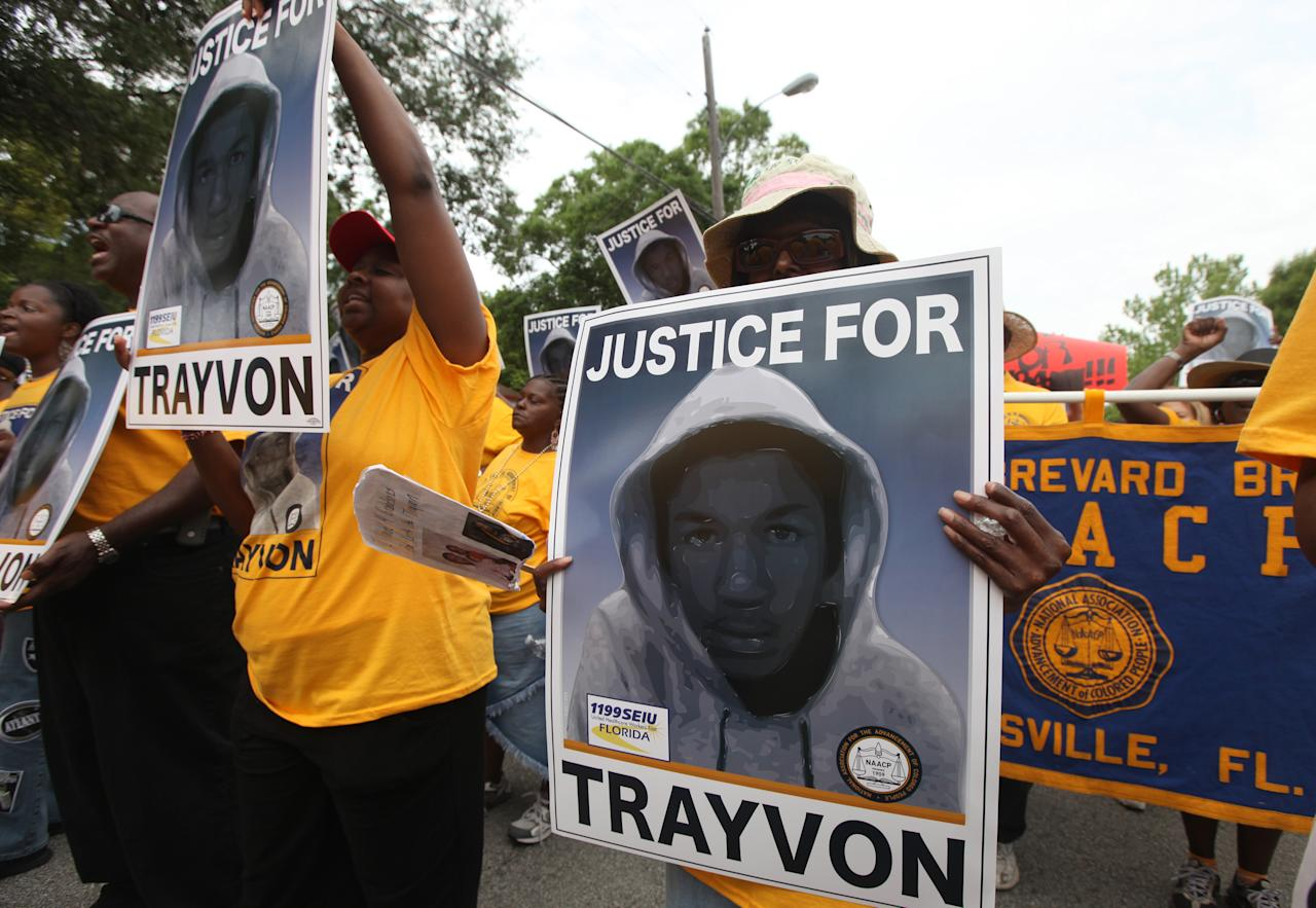 """Protestors hold up signs in a march and rally for slain Florida teenager Trayvon Martin on Saturday, March 31, 2012 in Sanford, Fla. Protesters carried signs, chanted """"Justice for Trayvon,"""" and clutched the hands of their children while they walked from Crooms Academy of Information Technology, the county's first high school for black students, to the Sanford Police Department. The march was organized by the NAACP was one of several taking place over the weekend. (AP Photo/Julie Fletcher)"""