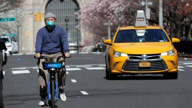 A man wearing a protective mask rides a bicycle on Park Avenue in midtown Manhattan during the outbreak of Covid-19 in New York City on March 24.