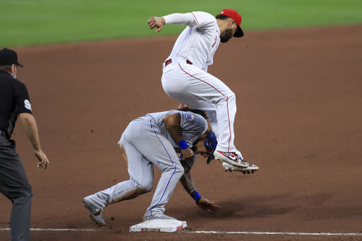 Cincinnati Reds' Eugenio Suarez (7) leaps over and applies the tag as Kansas City Royals' Adalberto Mondesi (27) steals third base safely on a wild pitch in the fourth inning during a baseball game at in Cincinnati, Wednesday, Aug. 12, 2020. (AP Photo/Aaron Doster)