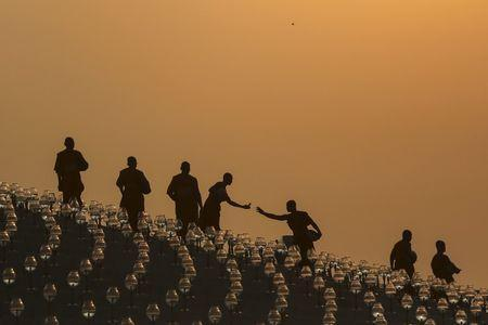 Buddhist monks prepare for an alms offering ceremony at the Wat Phra Dhammakaya temple in Pathum Thani province, north of Bangkok as the sun rises on Makha Bucha Day, in this March 4, 2015 file photo. REUTERS/Damir Sagolj/Files