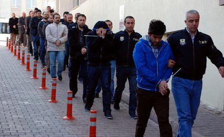 Suspected supporters of the U.S.-based cleric Gulen are escorted by plainclothes police officers as they arrive at the police headquarters in Kayseri