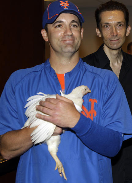 """New York Mets relief pitcher Tim Byrdak holds """"Little Jerry Seinfeld,"""" the chicken that he brought into the clubhouse before handing it off to representatives of the Farm Sanctuary of Watkins Glen, N.Y., before the Mets faced the New York Yankees in their interleague baseball game at Citi Field in New York, Sunday, June 24, 2012. (AP Photo/Kathy Willens)"""