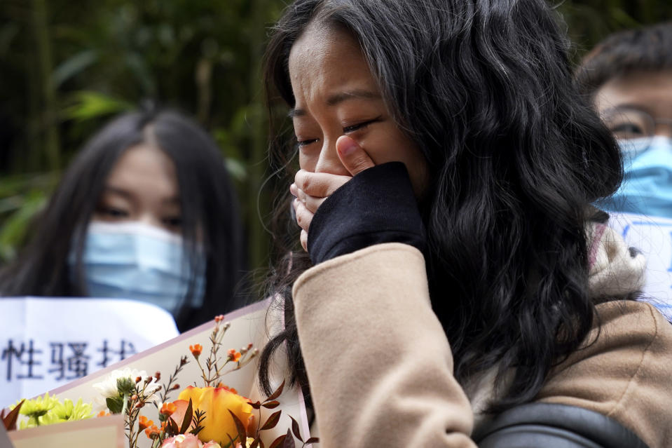 Zhou Xiaoxuan weeps as she speaks to her supporters upon arrival at a courthouse in Beijing, Wednesday, Dec. 2, 2020. Zhou, a Chinese woman who filed a sexual harassment lawsuit against a TV host, told dozens of cheering supporters at a courthouse Wednesday she hopes her case will encourage other victims of gender violence in a system that gives them few options to pursue complaints. (AP Photo/Andy Wong)