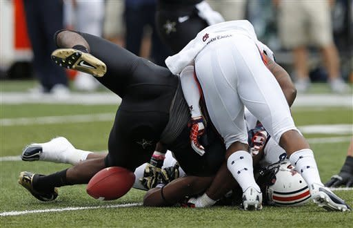 Vanderbilt running back Wesley Tate (24) fumbles after being hit by Auburn defensive lineman Angelo Blackson (98), and defensive back Jonathon Mincy, top, in the first quarter of an NCAA college football game on Saturday, Oct. 20, 2012, in Nashville, Tenn. (AP Photo/Joe Howell)