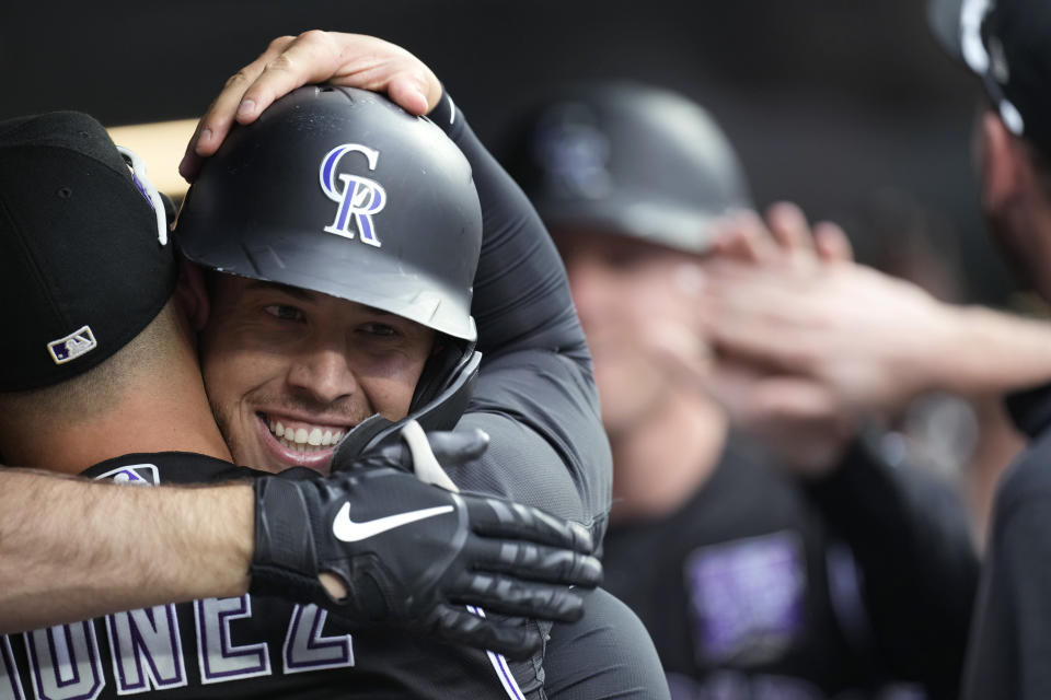Colorado Rockies' Dom Nunez, left, hugs C.J. Cron, who returns to the dugout after hitting a grand slam off Milwaukee Brewers starting pitcher Brandon Woodruff during the first inning of a baseball game Thursday, June 17, 2021, in Denver. (AP Photo/David Zalubowski)