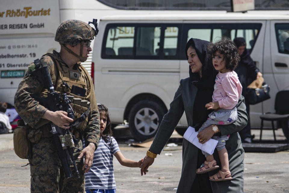 In this image provided by the U.S. Marine Corps, a Marine assigned to the 24th Marine Expeditionary Unit escorts evacuees at Hamid Karzai International Airport, in Kabul, Afghanistan, Friday, Aug. 20, 2021. (Cpl. Davis Harris/U.S. Marine Corps via AP)