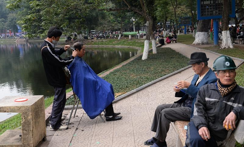 A Vietnamese street barber is seen servicing a customer at a park in central Hanoi (AFP Photo/Hoang Dinh Nam)