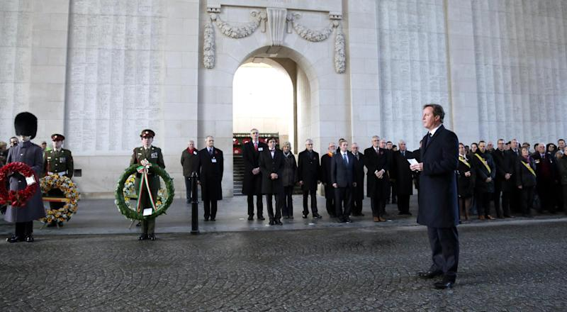 British Prime Minister David Cameron, center, reads the Ode of Remembrance at the Menin Gate in Ypres, Belgium on Thursday, Dec. 19, 2013. Both heads of state are visiting several World War One sites ahead of a four year Centenary program which begins in 2014. The Menin Gate is a war memorial dedicated to the British and Commonwealth soldiers who were killed in the Ypres Salient and whose graves are unknown. (AP Photo/Virginia Mayo)