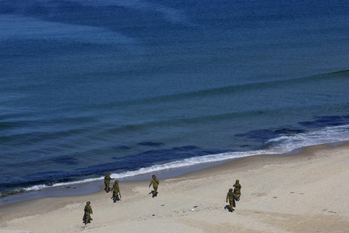 Palestinian militants patrol on the beach of the Mediterranean sea during a military drill organized by military factions outside Gaza City, Tuesday, Dec. 29, 2020. Palestinian militants in the Gaza Strip fired a salvo of rockets into the Mediterranean Sea on Tuesday as part of a self-styled military drill aimed at preparing for a possible war with Israel. (AP Photo/Adel Hana)
