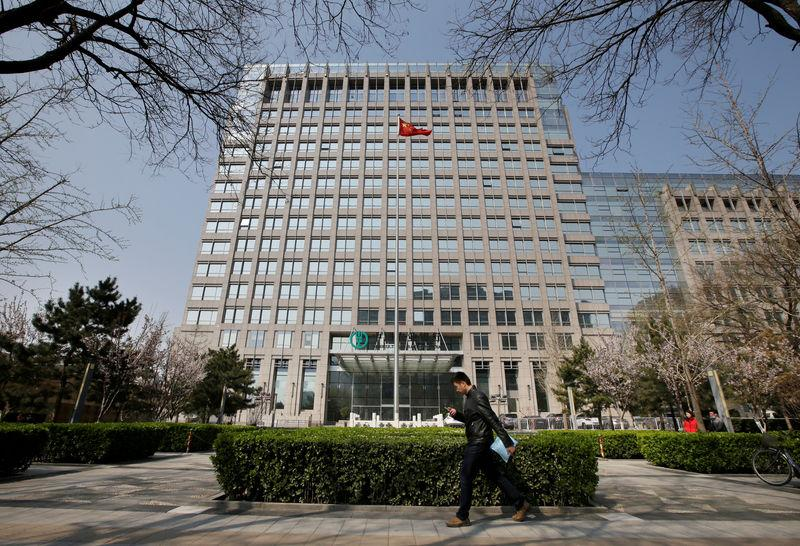 FILE PHOTO: Man walks past the headquarters of Agricultural Bank of China in Beijing