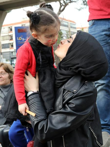 A Lebanese woman kisses her daughter as protesters gather outside the Supreme Shiite Council in Beiruit to demand a change in child custody laws that favour fathers over mothers in divorce cases