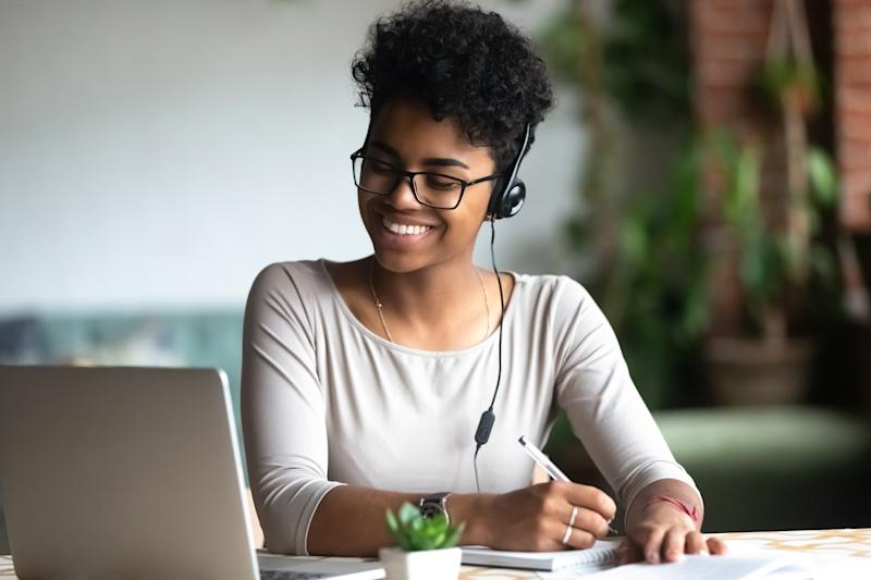 Smiling african American millennial female student in headphones and glasses sit at desk watch webinar making notes, happy biracial young woman in earphones work study using computer write in notebook