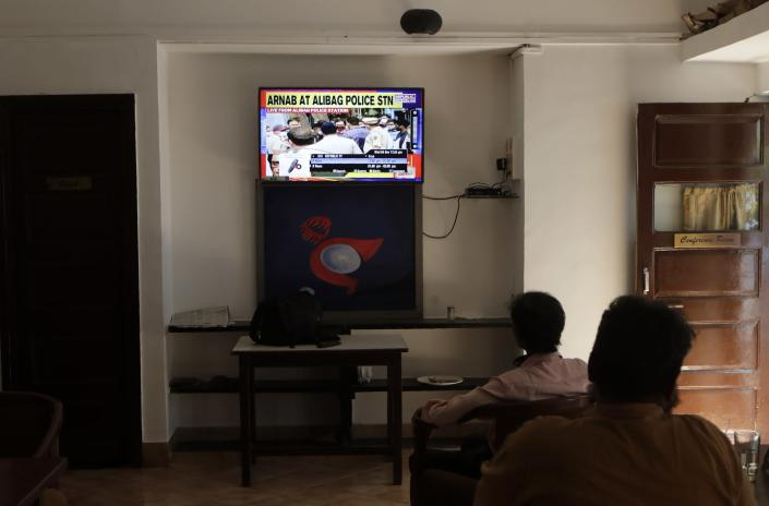 Journalists watch on television the news of the arrest of television news anchor Arnab Goswami at the Mumbai Press Club in Mumbai, India, Wednesday, Nov. 4, 2020. Indian police on Wednesday said they arrested the Republic TV founder and charged him with abetment to suicide in connection with the 2018 deaths of an interior designer and the designer's mother. (AP Photo/Rajanish Kakade)