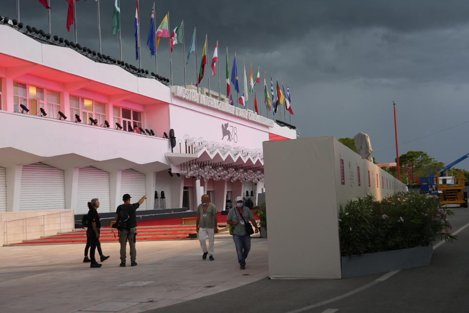 Workers walk by a wall hiding the red carpet of the 78th edition of the Venice Film Festival from the view of the public at the Venice Lido, Italy, Monday, Aug. 30, 2021. (AP Photo/Domenico Stinellis)