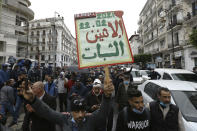 """Algerians demonstrate, one with a poster reading """"Resistance Monday"""" in Algiers as they mark the second anniversary of the Hirak movement, Monday Feb. 22, 2021. February 22 marks the second anniversary of Hirak, the popular movement that led to the fall of Algerian President Abdelaziz Bouteflika. (AP Photo/Anis Belghoul)"""