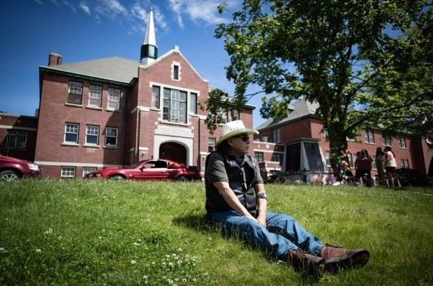 A residential school survivor sits on the lawn of the former Kamloops Residential School, in Kamloops, B.C., on Monday, May 31, 2021.